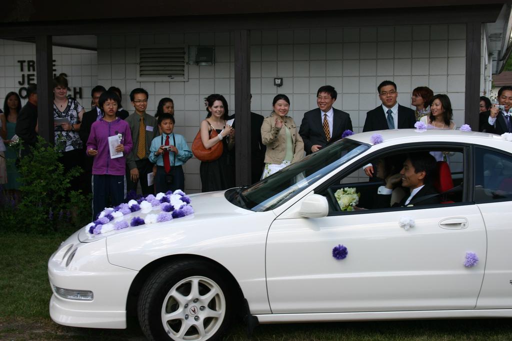 Украшение белой свадебной машины фиолетовыми цветами