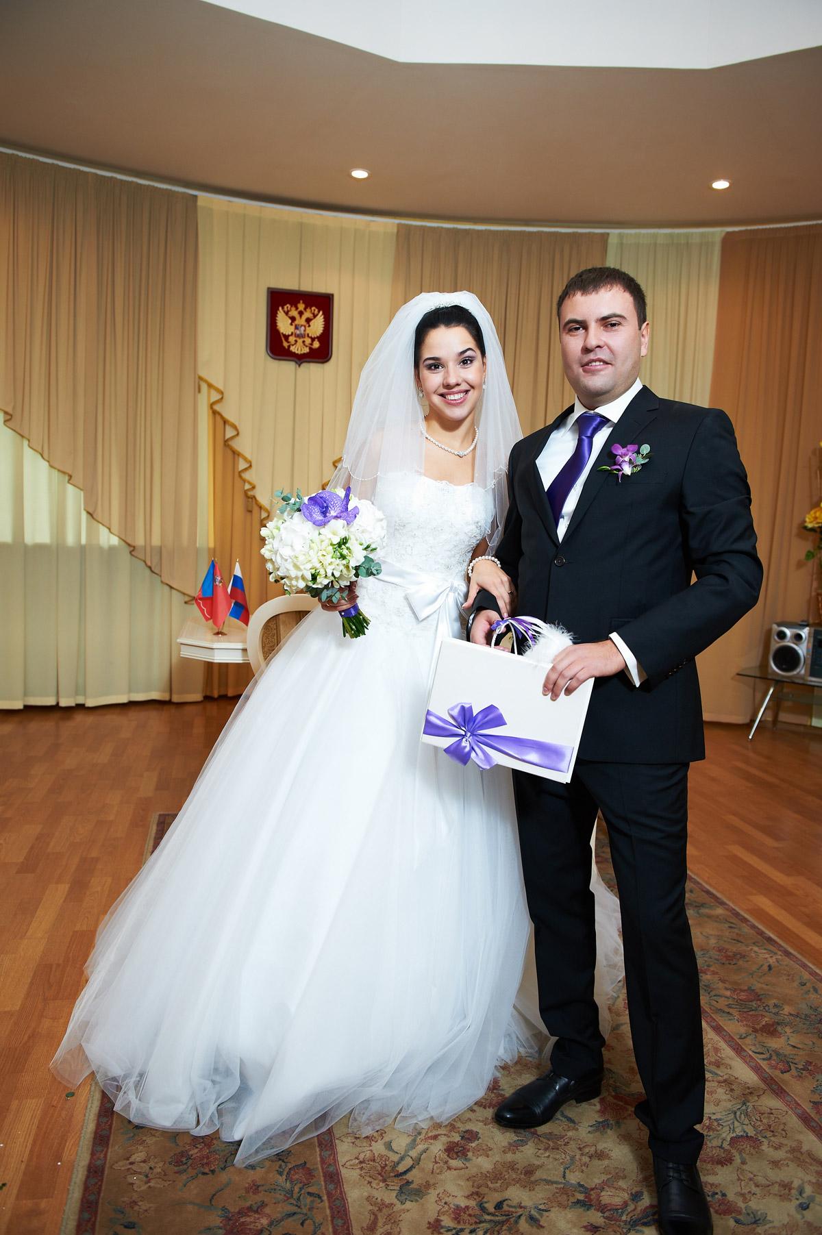 Папка для свидетельства о браке в руках молодоженов